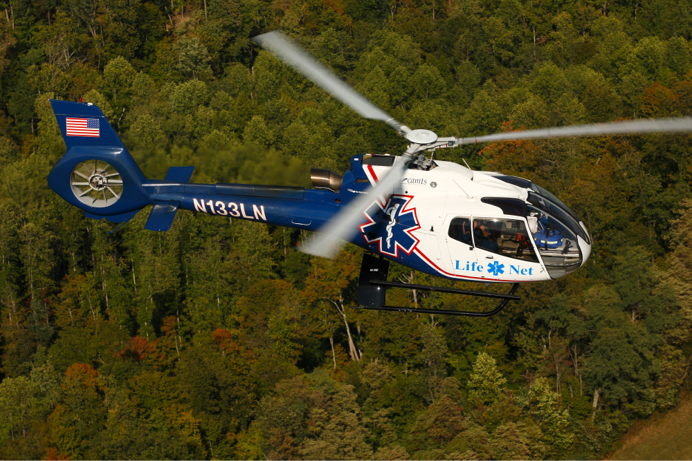 Air Methods helicopter flying over forest.